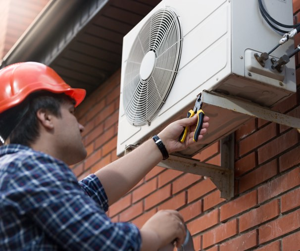 Outdoor AC unit with man repairing it