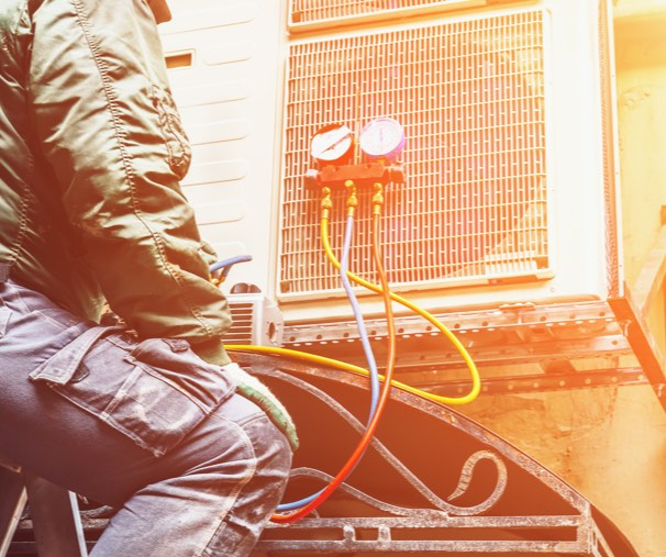 man looking at AC unit deciding to repair or replace